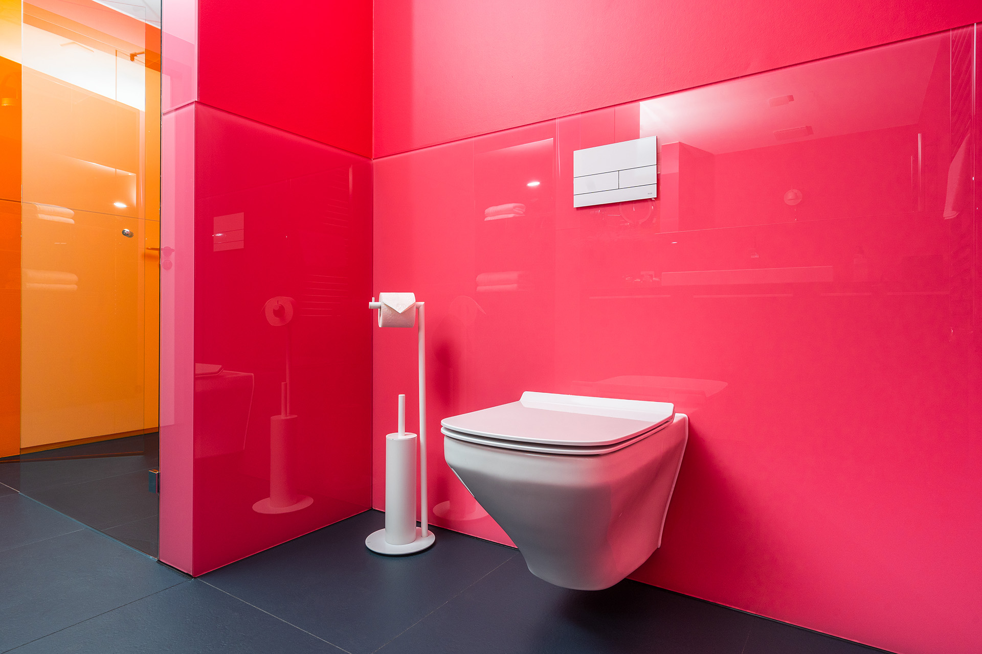 In glossy white, the TECEsquare II toilet flush plate appears here as an independent character that sets a cheeky highlight on the red wall.